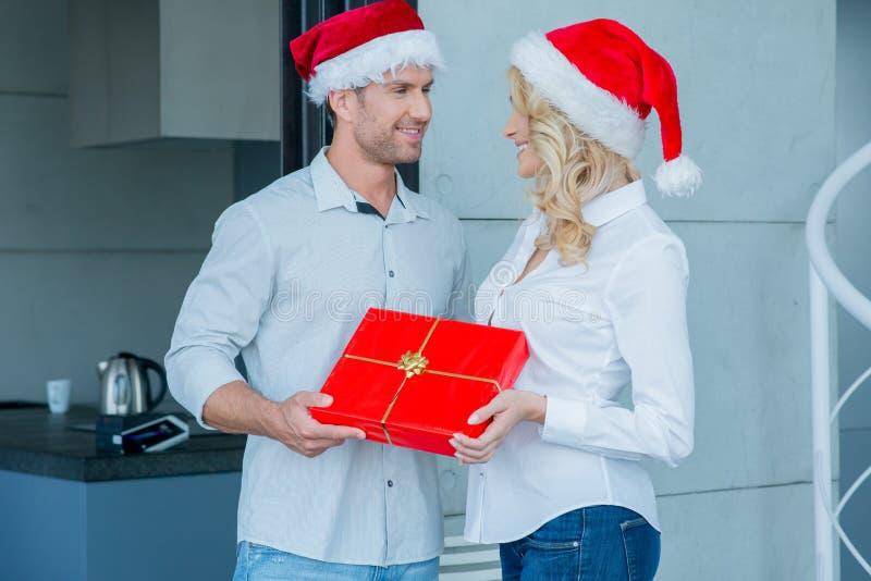 Coppie che indossano Santa Hats Exchanging Gift fotografie stock