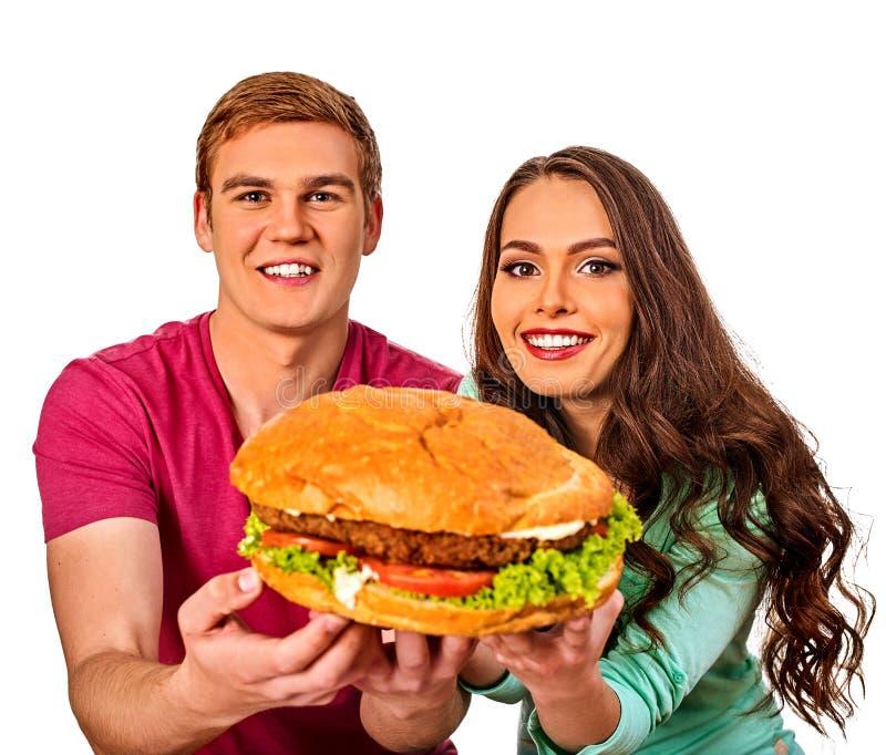 Coppie che mangiano alimenti a rapida preparazione Hamburger dell'ossequio della donna e dell'uomo immagini stock