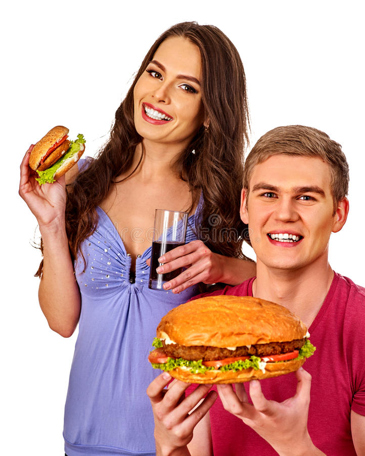 Coppie che mangiano alimenti a rapida preparazione Hamburger dell'ossequio della donna e dell'uomo fotografia stock libera da diritti