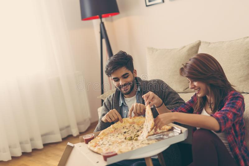 Coppie che mangiano pizza e divertiresi fotografia stock