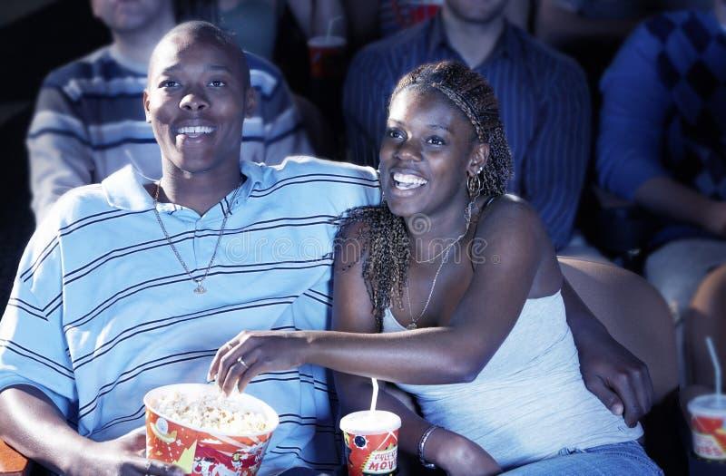 Coppie che mangiano popcorn mentre guardando film nel teatro fotografia stock