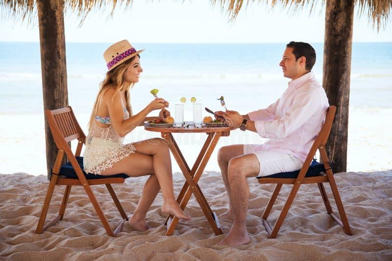 Coppie che mangiano pranzo alla spiaggia fotografie stock libere da diritti