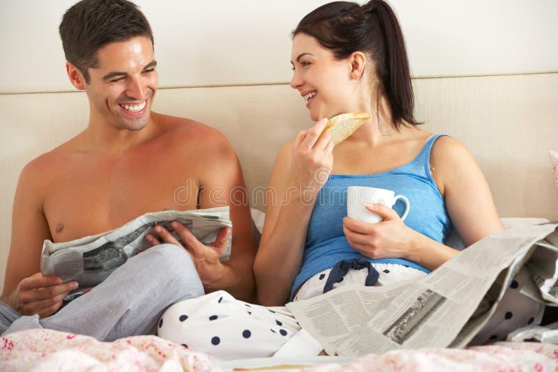 Coppie che mangiano prima colazione e che leggono giornale a letto fotografie stock libere da diritti