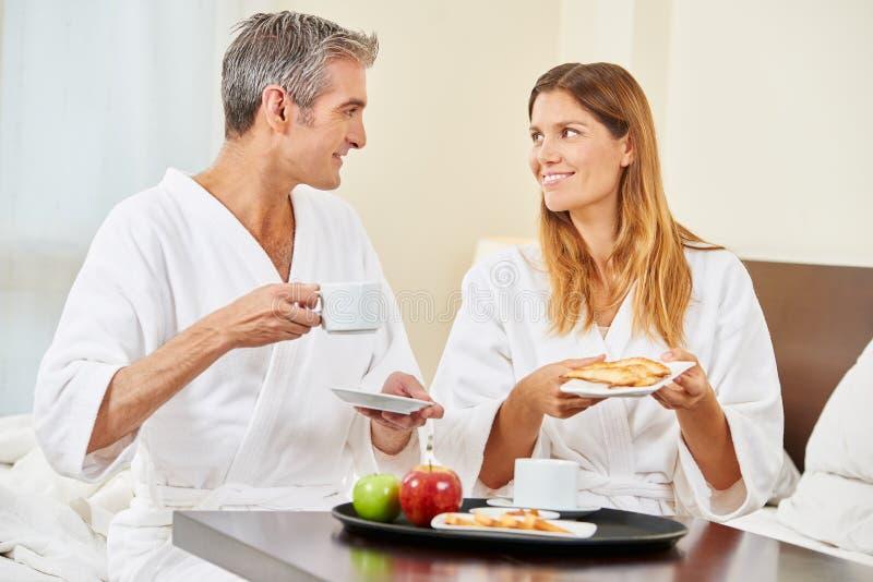 Coppie che mangiano prima colazione nella camera di albergo immagini stock libere da diritti