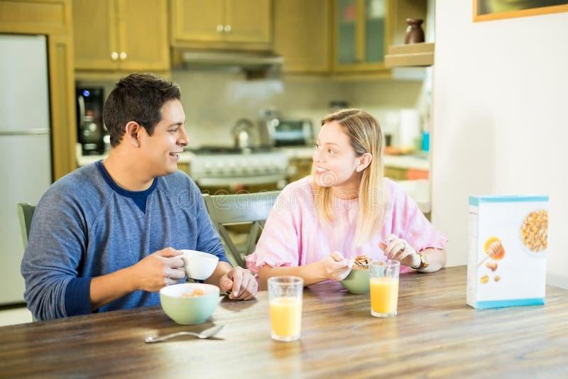 Coppie che mangiano prima colazione nella cucina fotografie stock