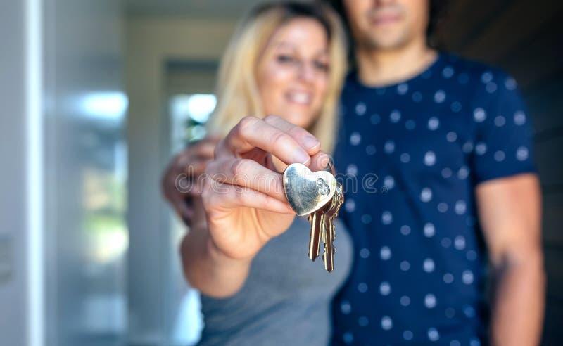 Coppie che mostrano le chiavi della loro casa fotografia stock