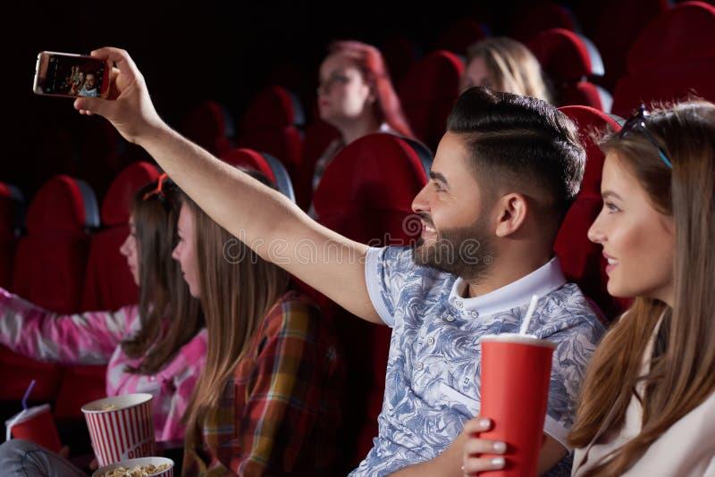 Coppie che prendono autoritratto allo Smart Phone in cinema fotografia stock libera da diritti