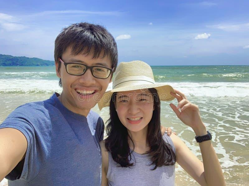 Coppie che prendono selfie alla spiaggia durante il viaggio di viaggio sull'aria aperta di vacanza di feste all'oceano o al mare  fotografia stock