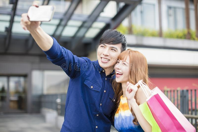 Coppie che prendono selfie davanti al centro commerciale immagini stock