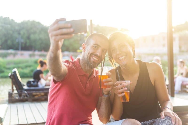 Coppie che prendono un selfie con le bevande fotografia stock libera da diritti