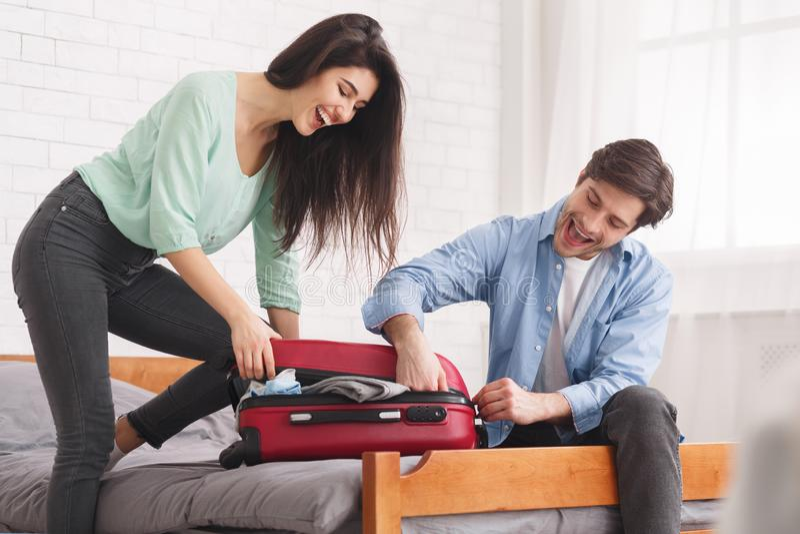 Coppie che provano a chiudere valigia piena in camera da letto immagine stock libera da diritti