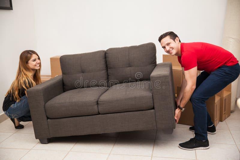 Coppie che provano a muovere un sofà fotografia stock libera da diritti