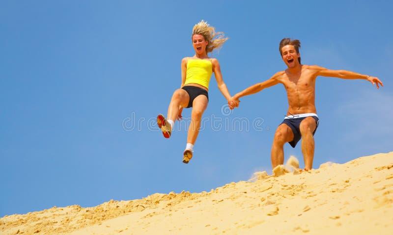 Coppie che saltano fuori dalla duna di sabbia immagini stock