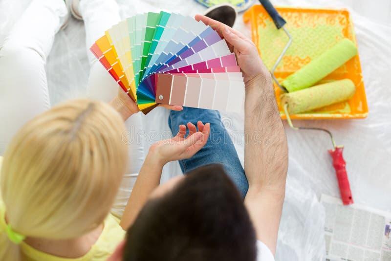 Coppie che scelgono i colori per dipingere nuova casa immagini stock libere da diritti