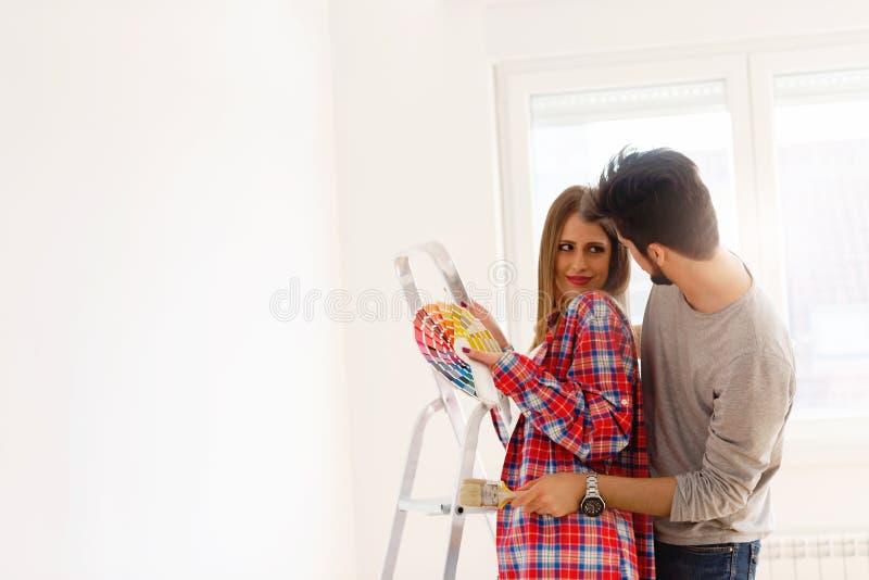 Coppie che scelgono i colori per la casa di verniciatura immagini stock libere da diritti