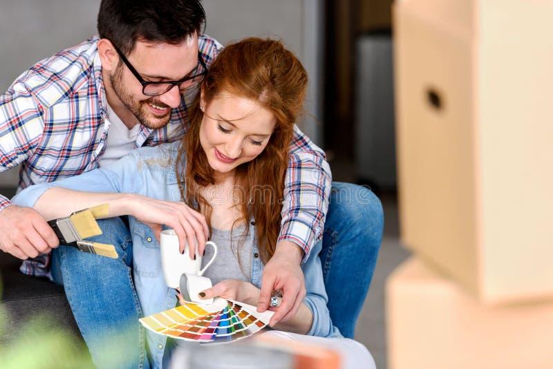 Coppie che scelgono i colori per la casa di verniciatura; divertiresi fotografia stock libera da diritti