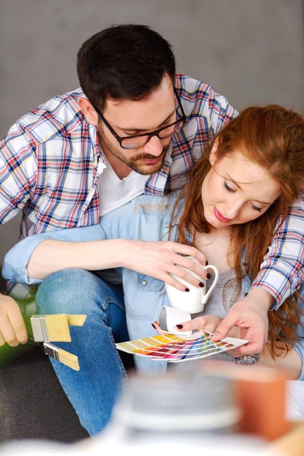 Coppie che scelgono i colori per la casa di verniciatura; divertiresi immagine stock libera da diritti