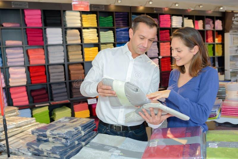Coppie che scelgono insieme i vestiti al mercato di modo immagine stock libera da diritti