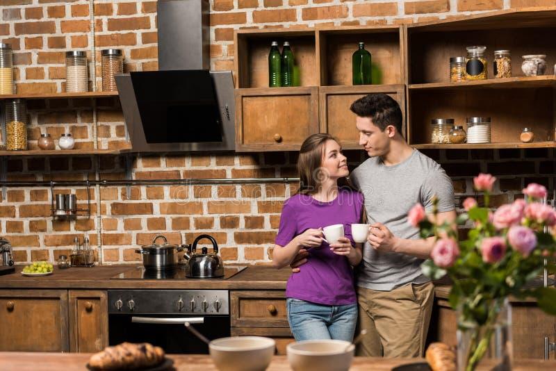 coppie che se esaminano in cucina e che tengono le tazze fotografia stock libera da diritti