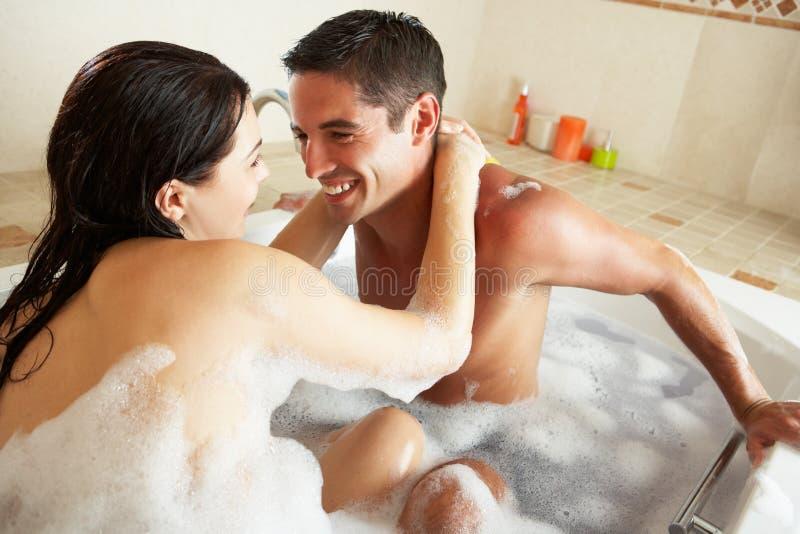 Coppie che si distendono nel bagno riempito bolla fotografia stock