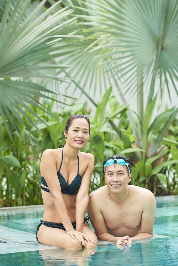 Coppie che si rilassano nella piscina dell'hotel immagine stock