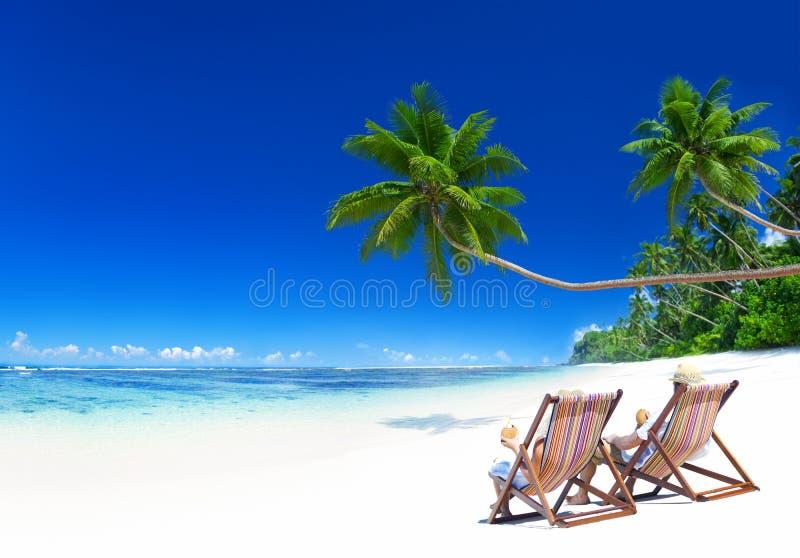 Coppie che si rilassano sulla spiaggia tropicale fotografia stock