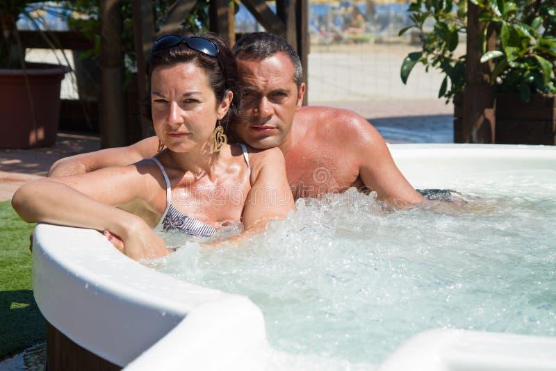 Coppie che si rilassano in vasca calda vacanza immagini stock libere da diritti