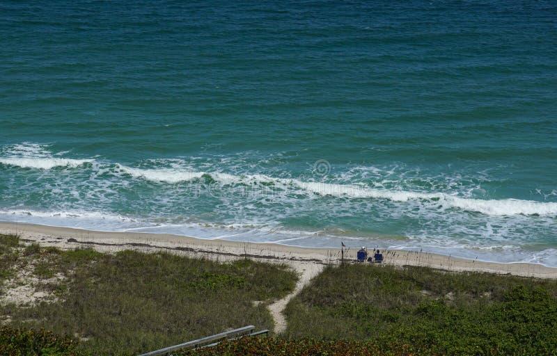 Coppie che si siedono alla spiaggia che esamina l'oceano immagine stock libera da diritti