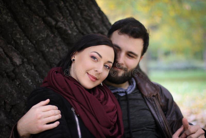 Coppie che si siedono da un albero fotografia stock libera da diritti