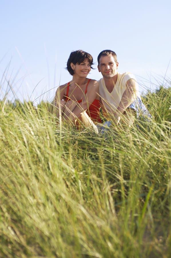Coppie che si siedono nell'erba alta fotografia stock
