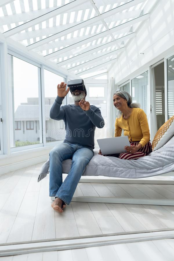 Coppie che si siedono su un letto mentre per mezzo dei dispositivi digitali fotografia stock libera da diritti