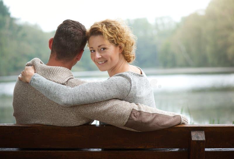 Coppie che si siedono sul banco da un lago fotografia stock libera da diritti