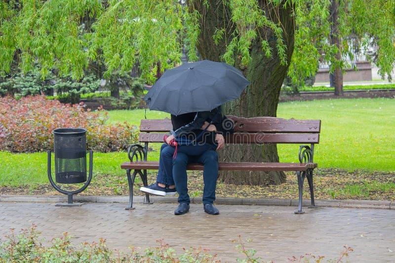 Coppie che si siedono sul banco nella pioggia immagine stock libera da diritti