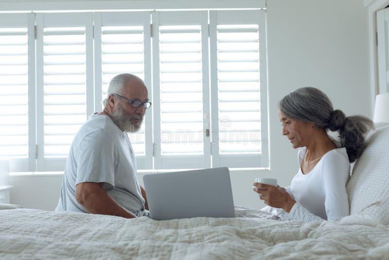 Coppie che si siedono sul letto dentro una stanza immagine stock