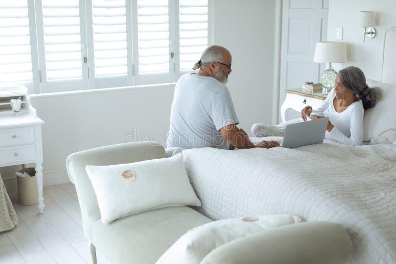 Coppie che si siedono sul letto dentro una stanza fotografia stock