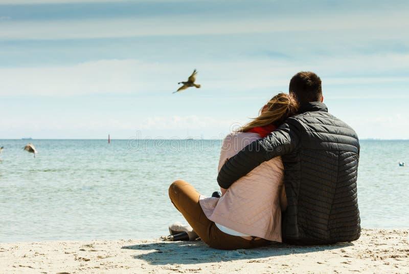Coppie che si siedono sulla retrovisione della spiaggia immagine stock