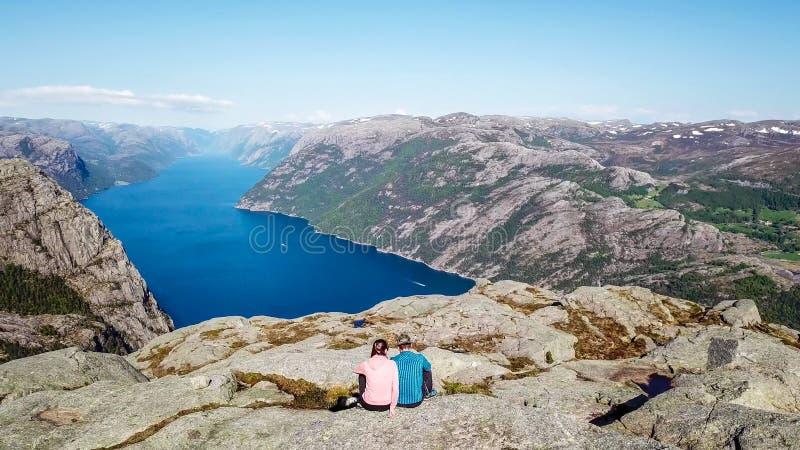 Coppie che si siedono sulla roccia che gode della vista del fiordo, vicino a Preikestolen, la Norvegia immagini stock libere da diritti