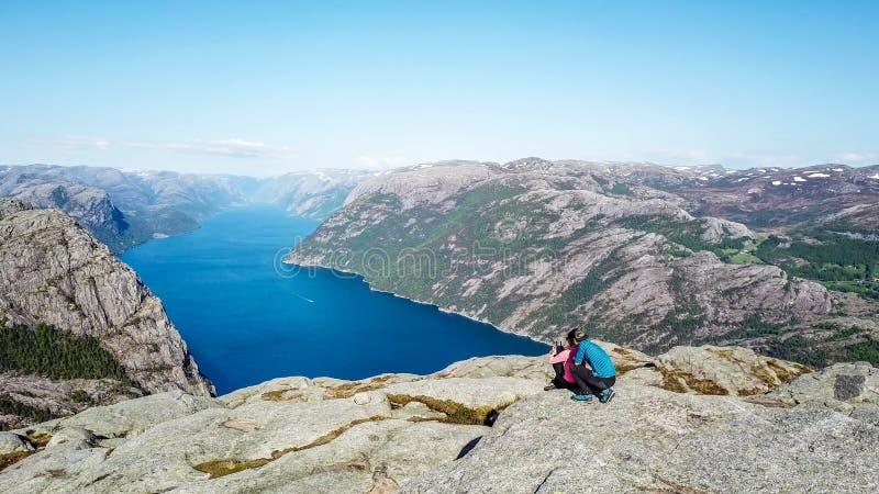 Coppie che si siedono sulla roccia che gode della vista del fiordo, vicino a Preikestolen, la Norvegia fotografie stock libere da diritti