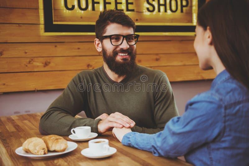 Coppie che si tengono per mano in caffè immagini stock libere da diritti