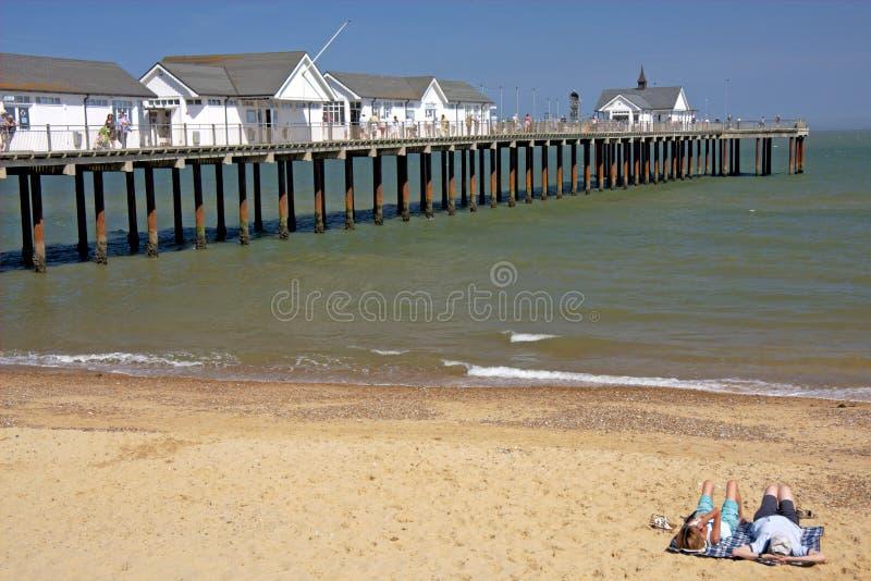 Coppie che si trovano sulla spiaggia, Inghilterra immagini stock libere da diritti