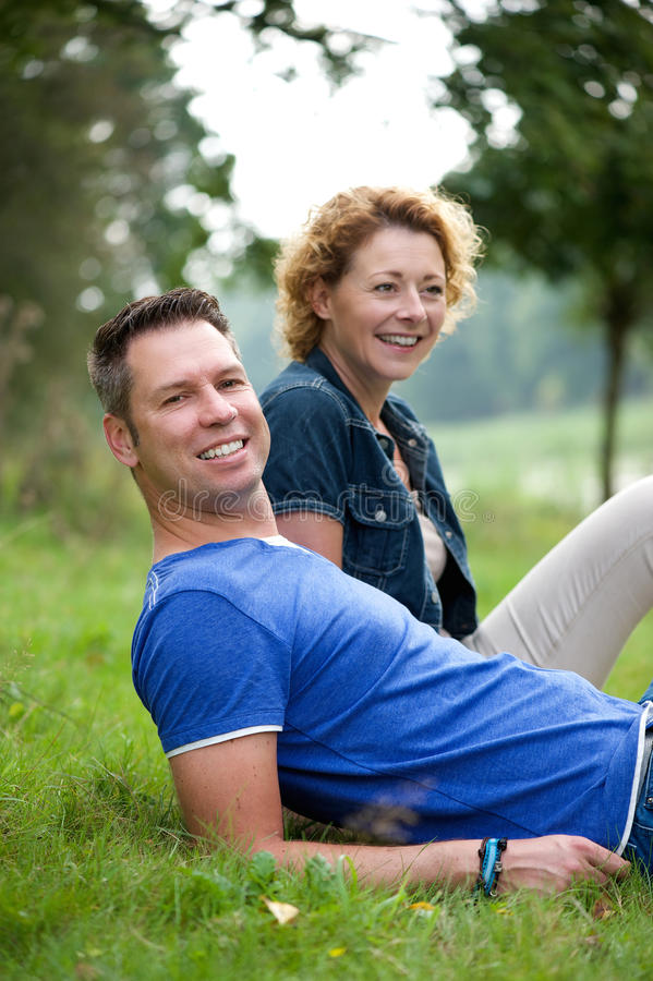 Coppie che sorridono e che si siedono sull'erba all'aperto fotografia stock libera da diritti