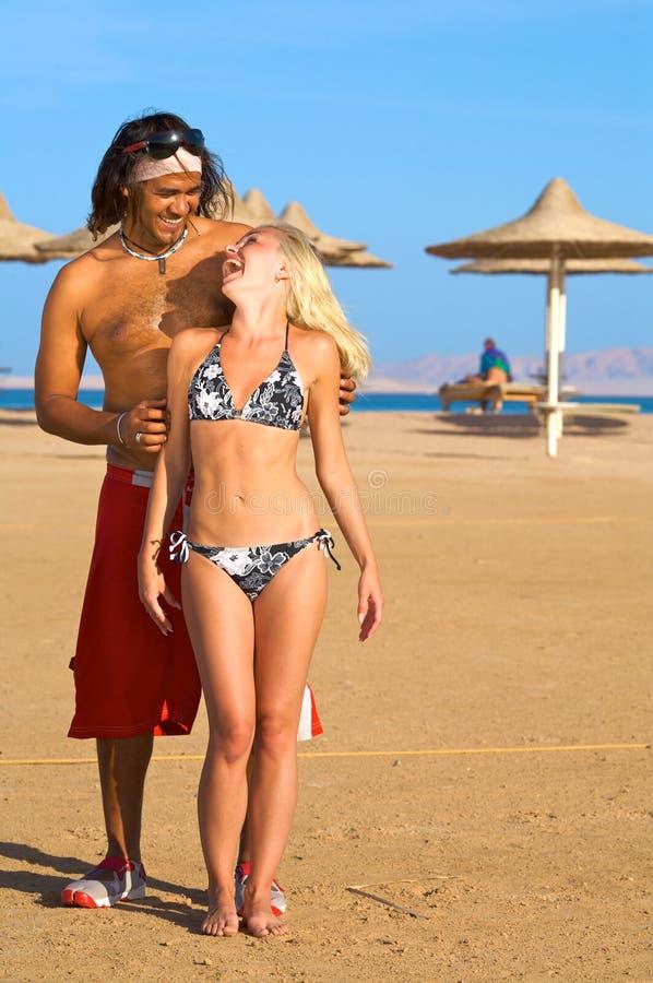 Coppie che sorridono sulla spiaggia fotografia stock libera da diritti