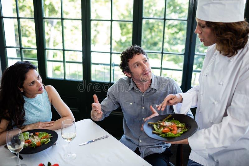 Coppie che sporgono querela circa l'alimento al cuoco unico immagine stock