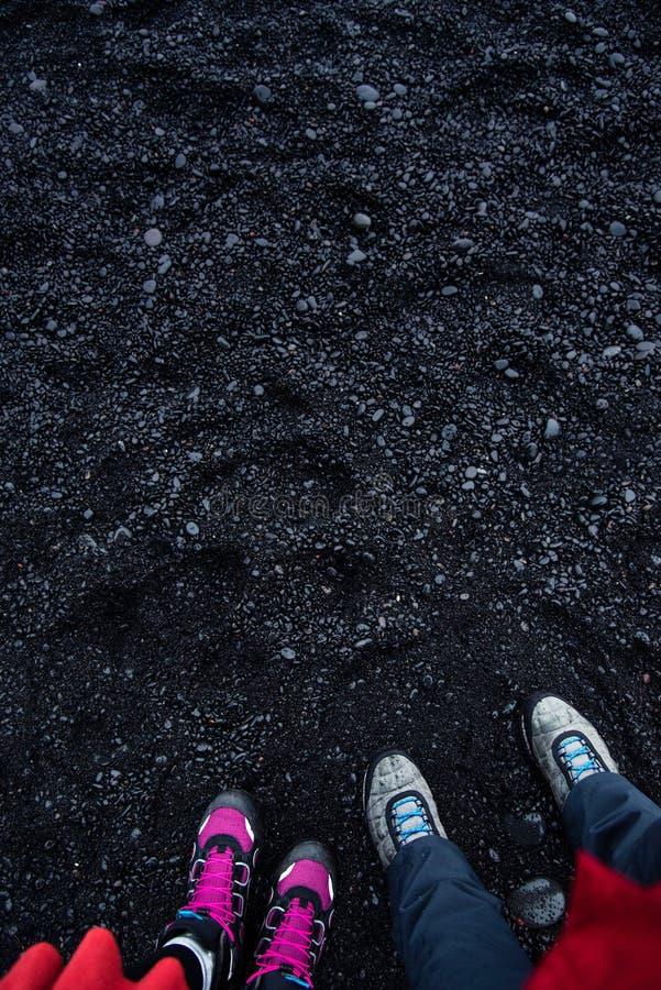 Coppie che stanno sulla spiaggia nera di Reynisfjara della sabbia in Islanda immagine stock libera da diritti