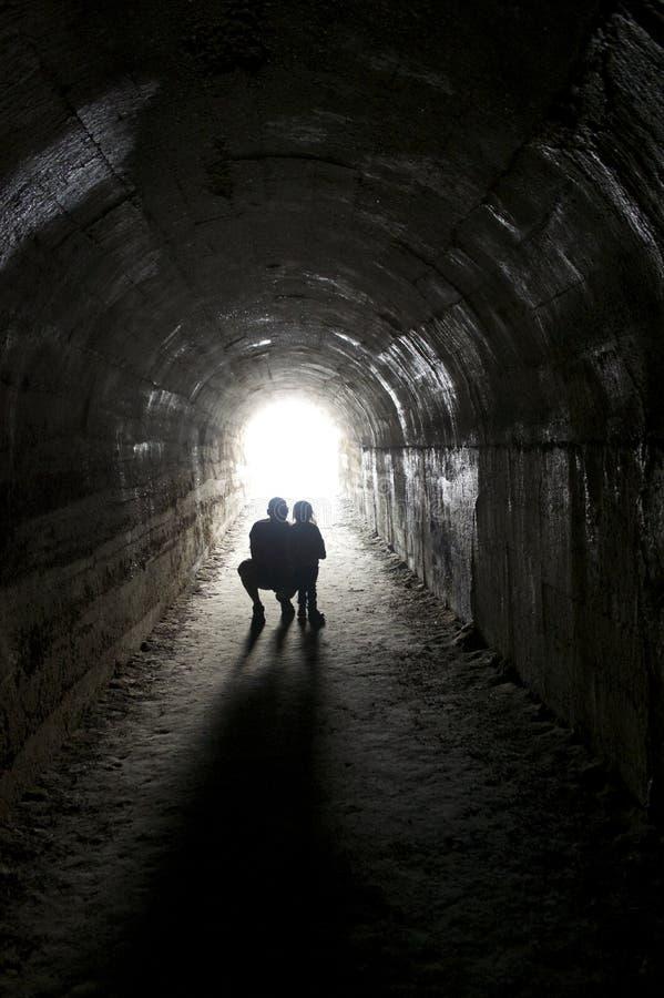 Coppie che stanno in tunnel, luce all'estremità di un tunnel fotografie stock