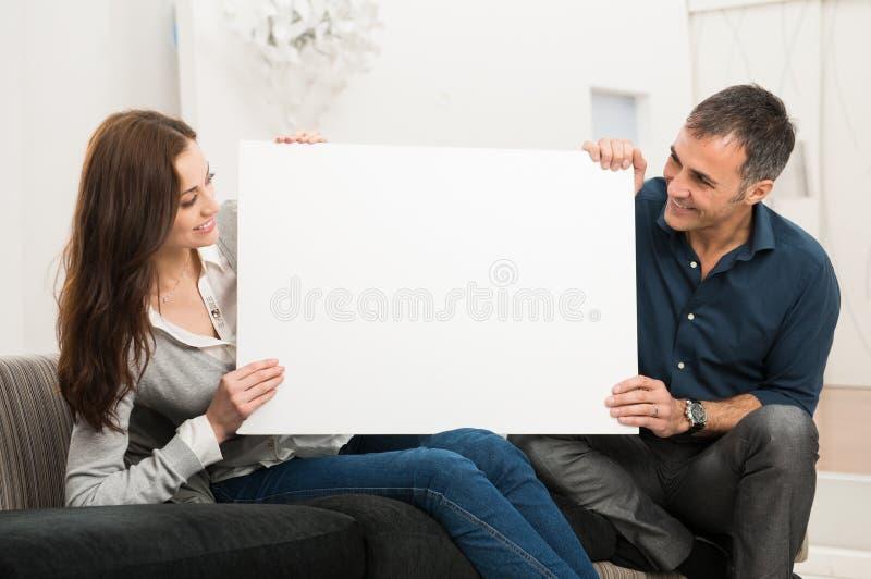 Coppie che tengono il cartello bianco del segno immagini stock libere da diritti