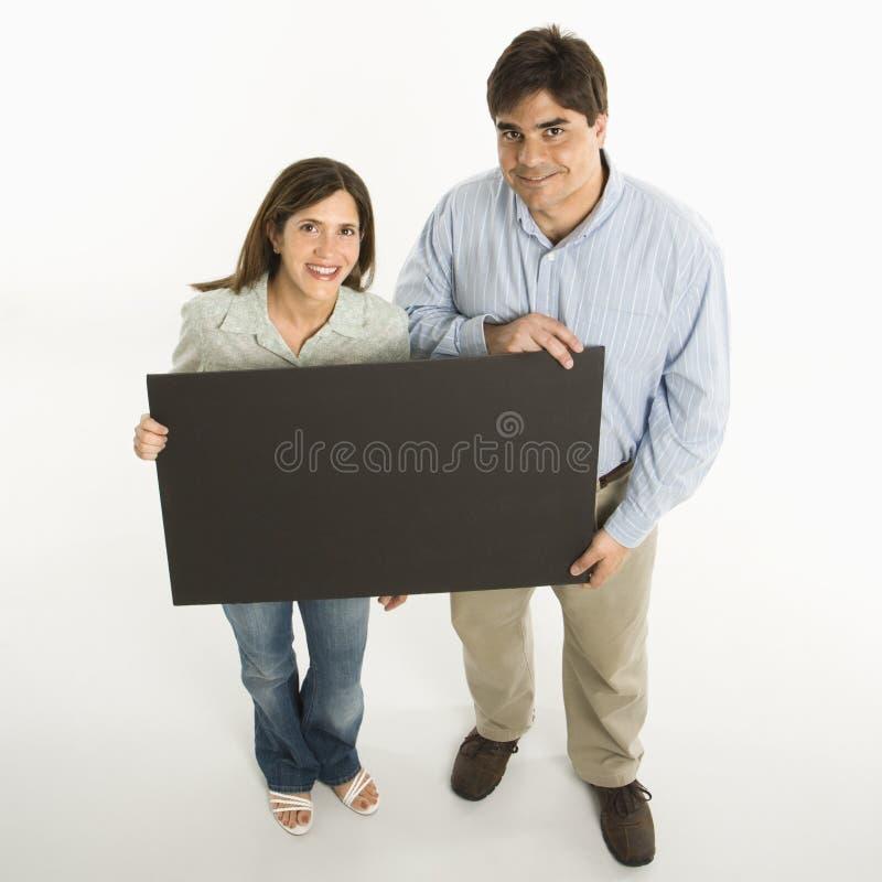 Coppie che tengono segno in bianco. fotografia stock libera da diritti
