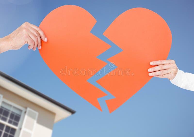 Coppie che tengono un cuore rotto fotografie stock