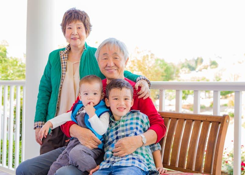 Coppie cinesi adulte senior attraenti che si siedono con la loro corsa mista Grandc immagini stock libere da diritti