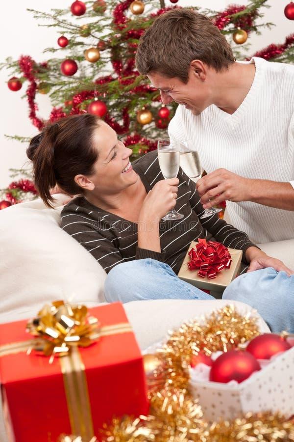 Coppie con champagne davanti all'albero di Natale immagini stock